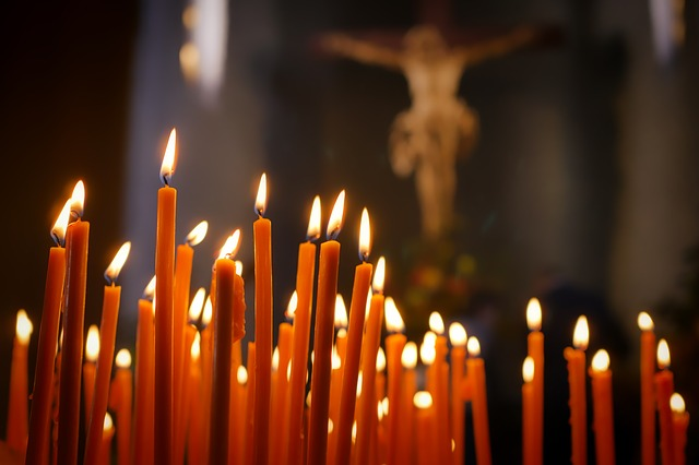 Group of lighted red candles often used in prayer; crucifix in background